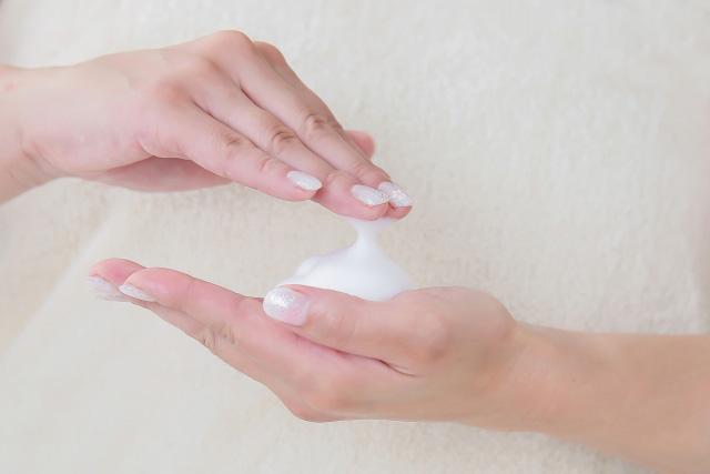 スクラブ洗顔フォームを泡立てる女性の手