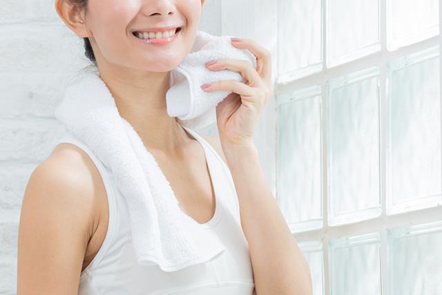 首の横に濡れタオルを当てて冷やす女性
